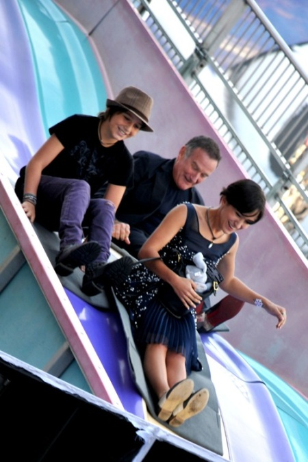 """Robin Williams rides down a slide with his kids Cody and Zelda at the """"Happy Feet Two"""" Premiere at the Grauman's Chinese Theater"""