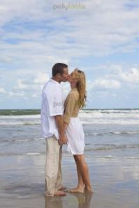 man_and_woman_couple_holding_hands_kissing_on_a_beach