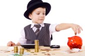 Little boy like a boss at the table counts money, isolated on white